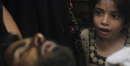 Eight-year-old Sumayya, whose uncle, Imran Ali, was injured in a shootout by unidentified gunmen, looks at him as he is brought to a hospital for treatment in Karachi August 23, 2011. The ongoing wave of violence has claimed nearly 100 lives in less than a week, local media reported. REUTERS